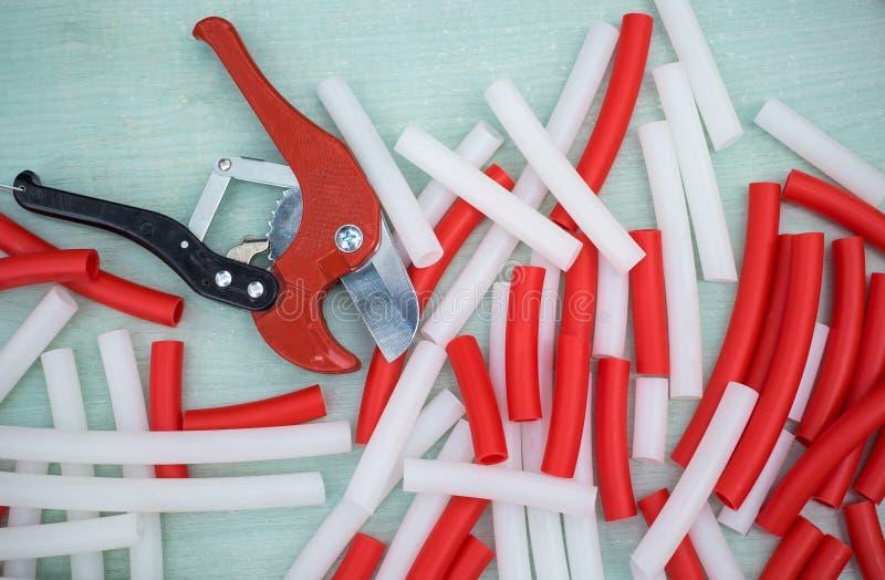 Κόκκινοι και άσπροι σωλήνες PVC για το θερμό πάτωμα Ψαλίδι για τα υδραυλικά στο ξύλινο υπόβαθρο στοκ εικόνες