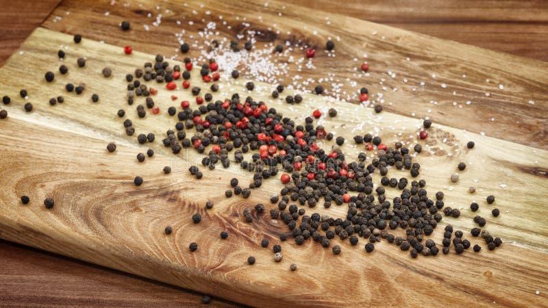 Κόκκινοι και μαύροι κόκκοι του πιπεριού και του αλατιού σε έναν ξύλινο πίνακα, έννοια καρυκευμάτων, έννοια μαγειρέματος στοκ εικόνα