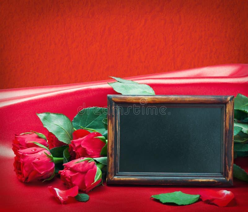 Κόκκινοι τριαντάφυλλα και πίνακας με το διάστημα για το κείμενο στοκ φωτογραφίες
