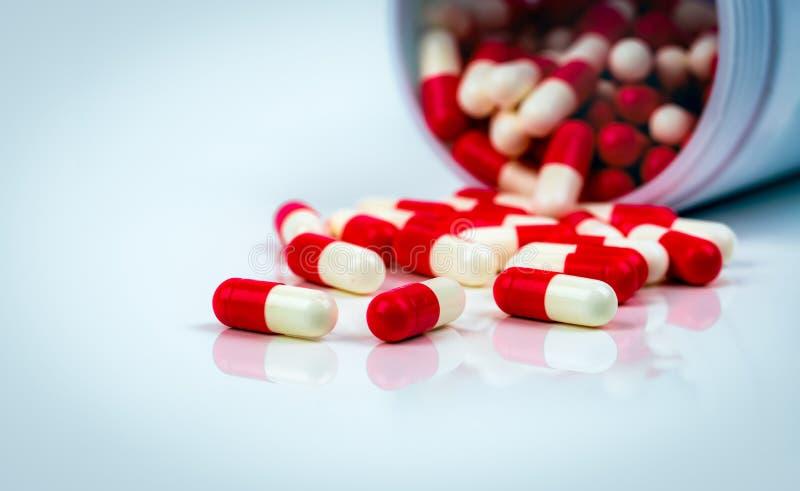 Κόκκινος-άσπρα χάπια καψών στον άσπρο πίνακα στο θολωμένο υπόβαθρο του μπουκαλιού φαρμάκων Αντίσταση φαρμάκων αντιβιοτικών Αντιμι στοκ φωτογραφία με δικαίωμα ελεύθερης χρήσης