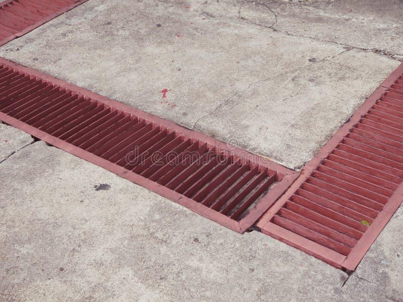 Κόκκινος αγωγός θύελλας υπονόμων οδών αποξηράνσεων σχαρών υδρορροών στοκ εικόνα με δικαίωμα ελεύθερης χρήσης