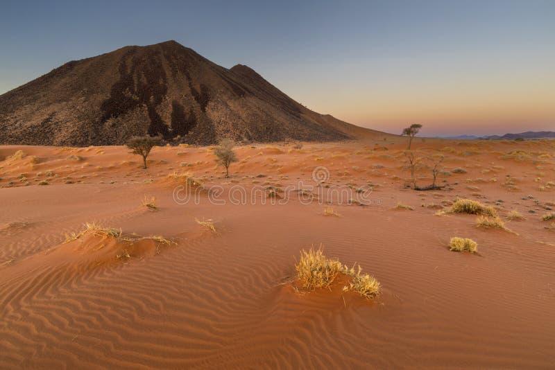 Κόκκινος αμμόλοφος άμμου και μαύρο βουνό βράχου στοκ φωτογραφία με δικαίωμα ελεύθερης χρήσης