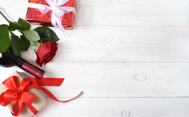Κόκκινος αυξήθηκε, ένα μπουκάλι του κρασιού και δώρα στοκ φωτογραφία με δικαίωμα ελεύθερης χρήσης