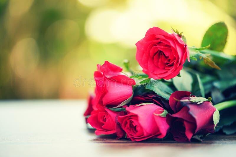 Κόκκινος αυξήθηκε ανθοδέσμη λουλουδιών/ρόδινη και κόκκινη αγάπη ημέρας βαλεντίνων τριαντάφυλλων στην ξύλινη επιτραπέζια φύση στοκ φωτογραφίες