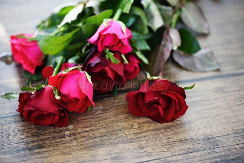 Κόκκινος αυξήθηκε ανθοδέσμη λουλουδιών/ρόδινη και κόκκινη αγάπη ημέρας βαλεντίνων τριαντάφυλλων στον ξύλινο πίνακα στοκ εικόνα