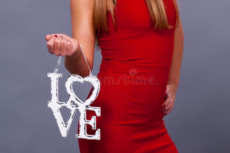 κόκκινος αυξήθηκε Γυναίκα που φορά το κόκκινο symbo αγάπης σημαδιών εκμετάλλευσης φορεμάτων στοκ εικόνες