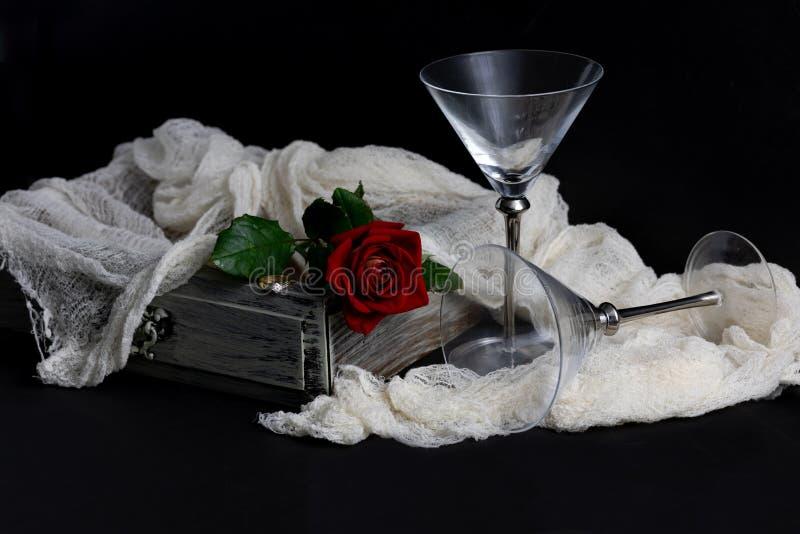 Κόκκινος αυξήθηκε, δαχτυλίδι διαμαντιών και γυαλιά κρασιού σε ένα μαύρο υπόβαθρο στοκ εικόνα με δικαίωμα ελεύθερης χρήσης