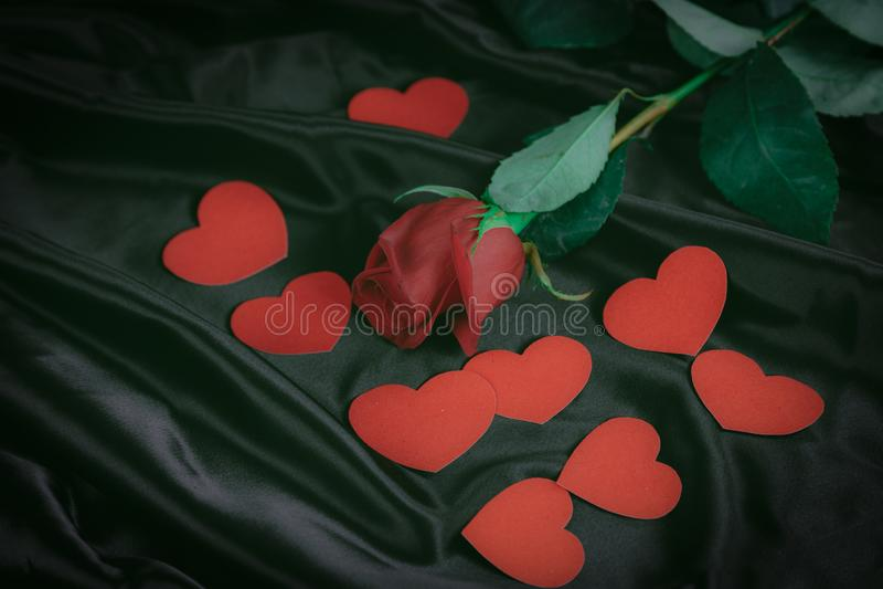 Κόκκινος αυξήθηκε και καρδιές στο μαύρο υπόβαθρο μεταξιού στοκ φωτογραφία με δικαίωμα ελεύθερης χρήσης
