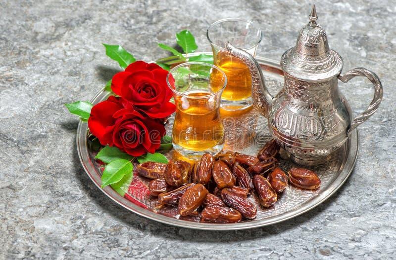 Κόκκινος αυξήθηκε λουλούδια με το τσάι και χρονολογεί τα φρούτα Ισλαμικές διακοπές RA στοκ φωτογραφία
