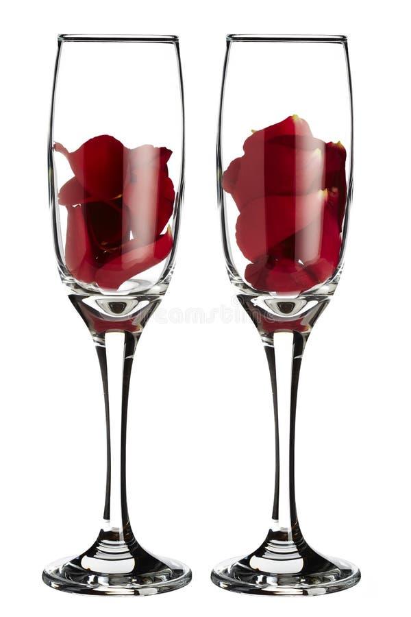 Κόκκινος αυξήθηκε πέταλα μέσα σε 2 γυαλιά σαμπάνιας στοκ φωτογραφία με δικαίωμα ελεύθερης χρήσης