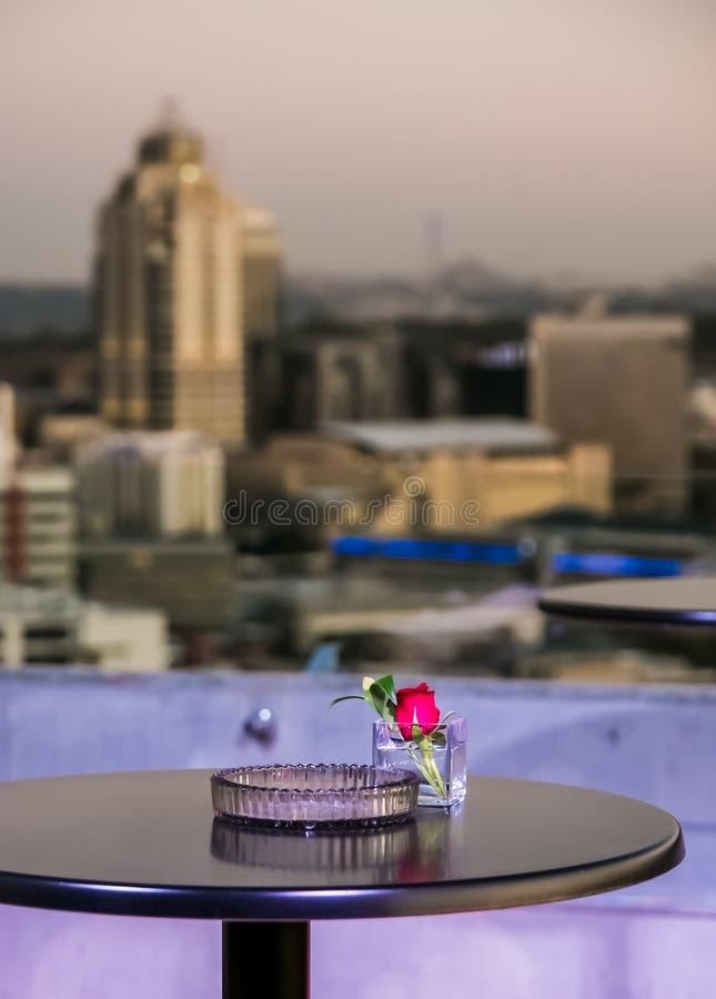 Κόκκινος αυξήθηκε σε ένα τετραγωνικό γυαλί επίδειξης στο μπαλκόνι ηλιοβασιλέματος στοκ φωτογραφίες με δικαίωμα ελεύθερης χρήσης