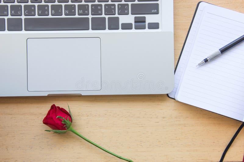 Κόκκινος αυξήθηκε, σημειωματάριο, μολύβι και lap-top στον ξύλινο πίνακα για την αγάπη γ στοκ φωτογραφία με δικαίωμα ελεύθερης χρήσης