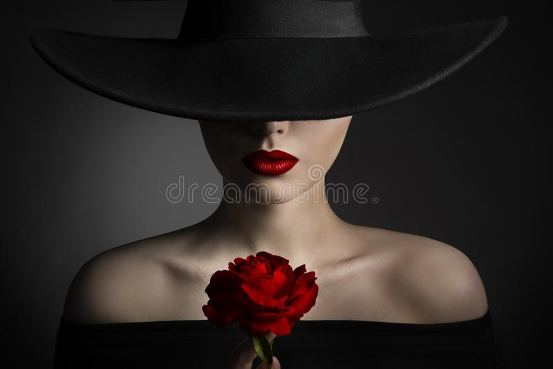 Κόκκινος αυξήθηκε χείλια γυναικών λουλουδιών και μαύρο καπέλο, πρότυπη ομορφιά μόδας στοκ φωτογραφίες