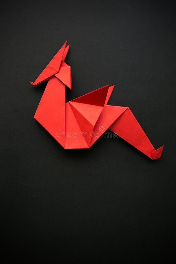 Κόκκινος διπλωμένος έγγραφο polygonal γεωμετρικός δράκος origami στο μαύρο υπόβαθρο Κενό διάστημα για το αντίγραφο, κείμενο, εγγρ στοκ εικόνα