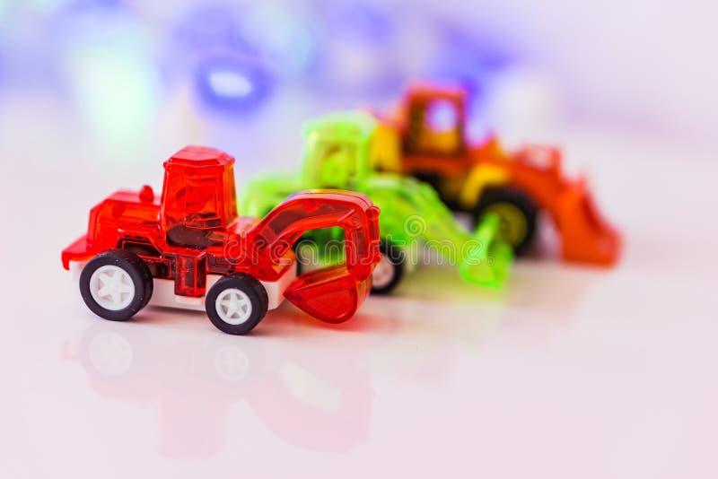 Κόκκινος εκσκαφέας παιχνιδιών και δύο φορτωτές, υπόβαθρο bokeh MO έννοιας στοκ εικόνες με δικαίωμα ελεύθερης χρήσης