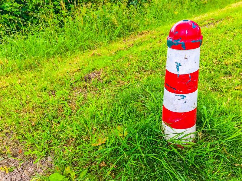 Κόκκινος και άσπρος ριγωτός πόλος ορόσημων σε ένα τοπίο χλόης στοκ εικόνες