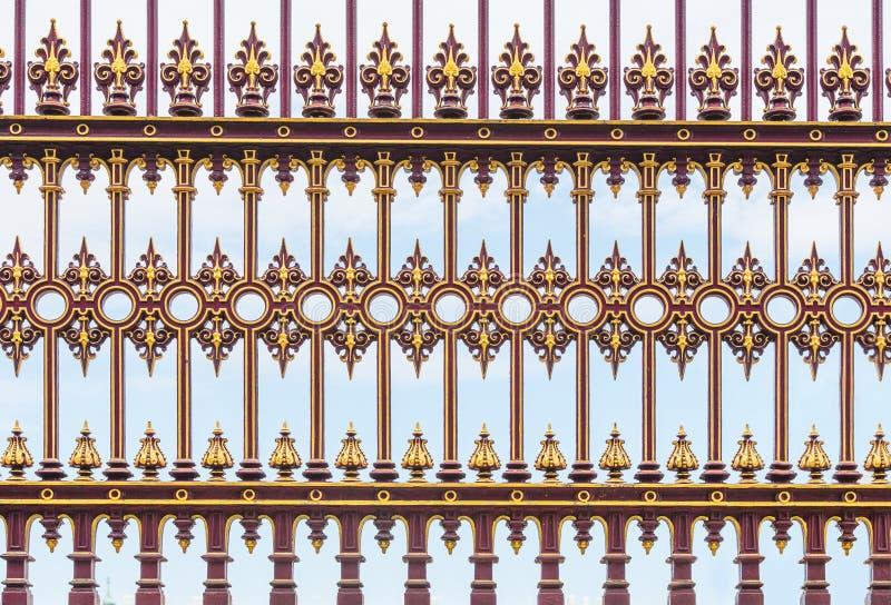 Κόκκινος και χρυσός το υπόβαθρο φρακτών σιδήρου στοκ εικόνα με δικαίωμα ελεύθερης χρήσης