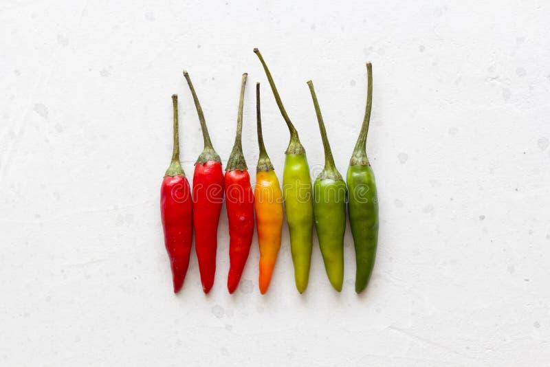 Κόκκινος - καυτά πιπέρια τσίλι στο υπόβαθρο ή τον άσπρο πίνακα Πολλά κόκκινα πιπέρια τσίλι Πράσινα, κίτρινα καυτά πιπέρια τσίλι Δ στοκ φωτογραφία με δικαίωμα ελεύθερης χρήσης