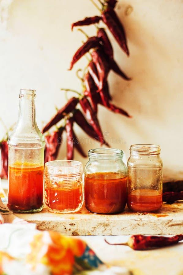 Κόκκινος - καυτή γλυκιά σάλτσα τσίλι πέρα από το παλαιό άσπρο ξύλινο υπόβαθρο Rus στοκ εικόνες με δικαίωμα ελεύθερης χρήσης