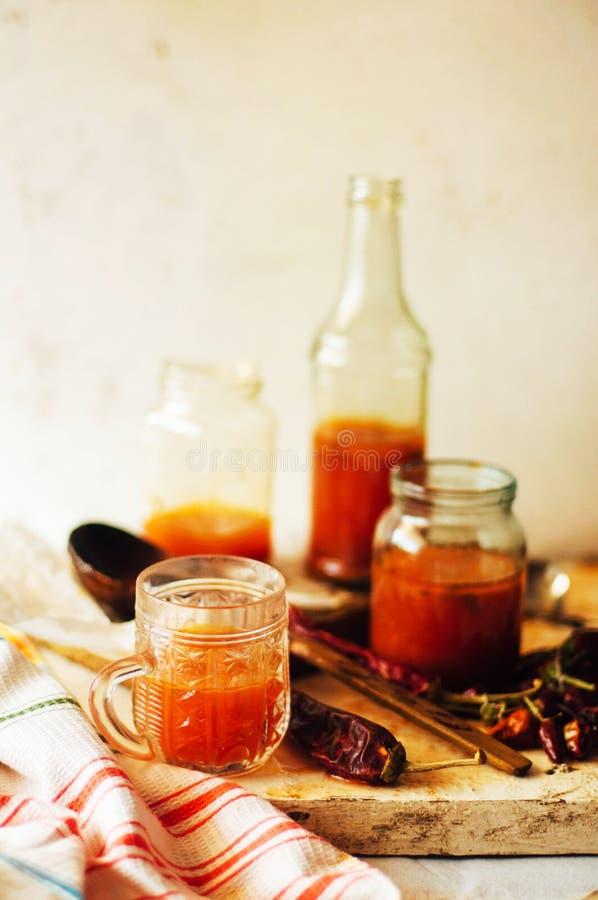 Κόκκινος - καυτή γλυκιά σάλτσα τσίλι πέρα από το παλαιό άσπρο ξύλινο υπόβαθρο Rus στοκ εικόνες