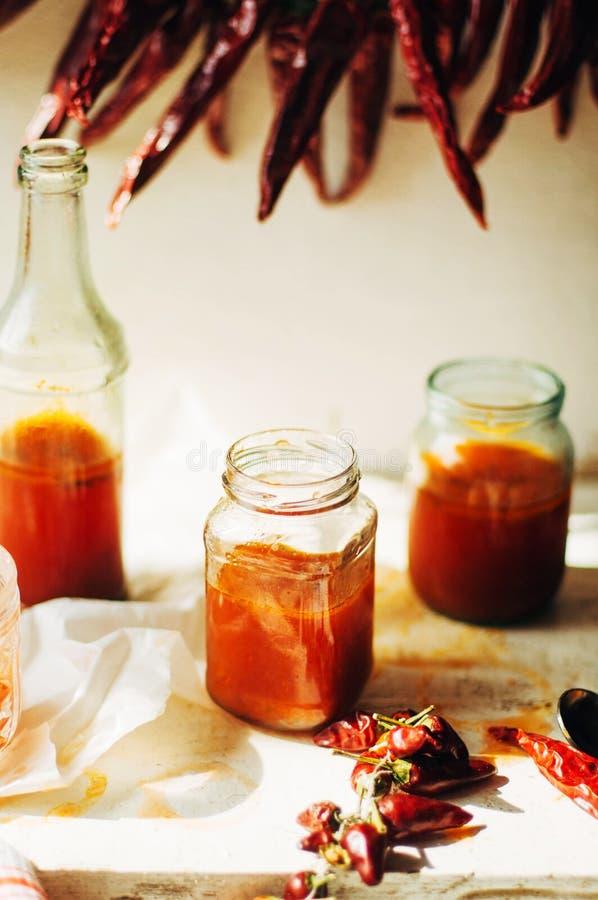 Κόκκινος - καυτή γλυκιά σάλτσα τσίλι πέρα από το παλαιό άσπρο ξύλινο υπόβαθρο Rus στοκ φωτογραφία
