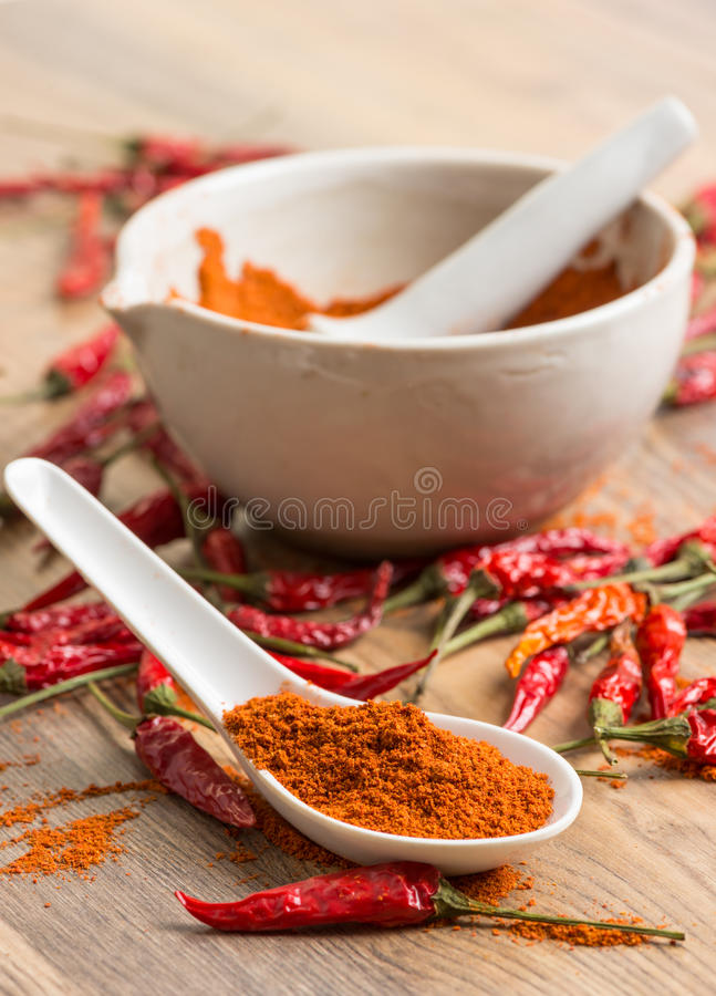 Κόκκινος - καυτή σκόνη τσίλι πιπεριών σε ένα κονίαμα και τους λοβούς στοκ εικόνες με δικαίωμα ελεύθερης χρήσης