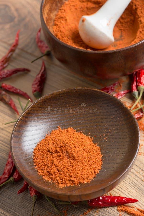 Κόκκινος - καυτή σκόνη τσίλι πιπεριών σε ένα κονίαμα και τους λοβούς στοκ φωτογραφίες με δικαίωμα ελεύθερης χρήσης