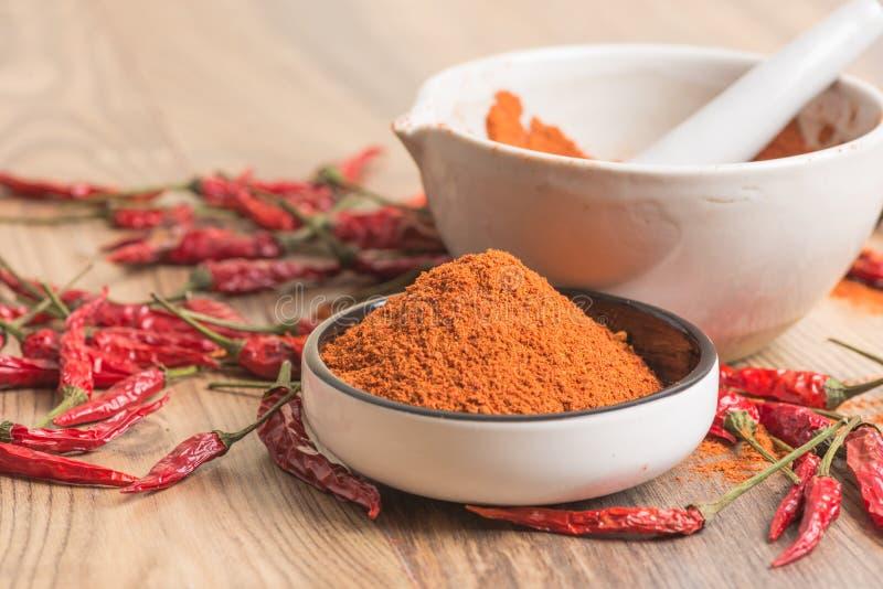 Κόκκινος - καυτή σκόνη τσίλι πιπεριών σε ένα κονίαμα και τους λοβούς στοκ φωτογραφία με δικαίωμα ελεύθερης χρήσης