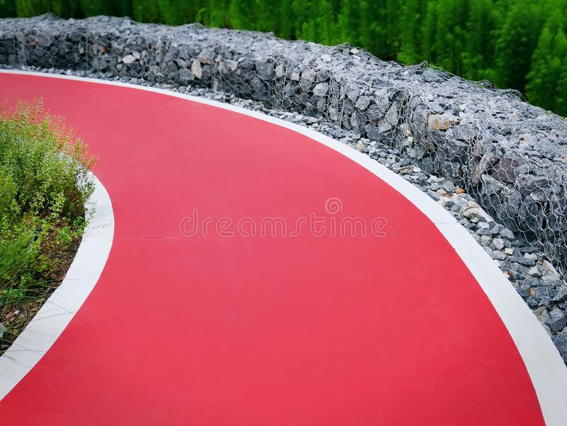Κόκκινος κυρτός ενιαίος δρόμος παρόδων με τους βράχους ως φράκτη στοκ εικόνες με δικαίωμα ελεύθερης χρήσης