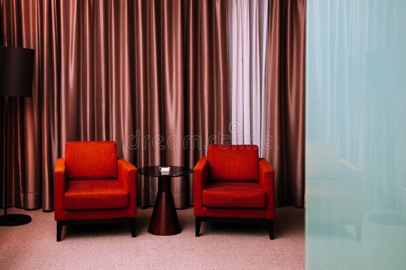 Κόκκινος ξενοδοχείων καναπές πολυθρόνων ύφους σύγχρονος με το μαύρους πίνακα και το πάτωμα στοκ εικόνες