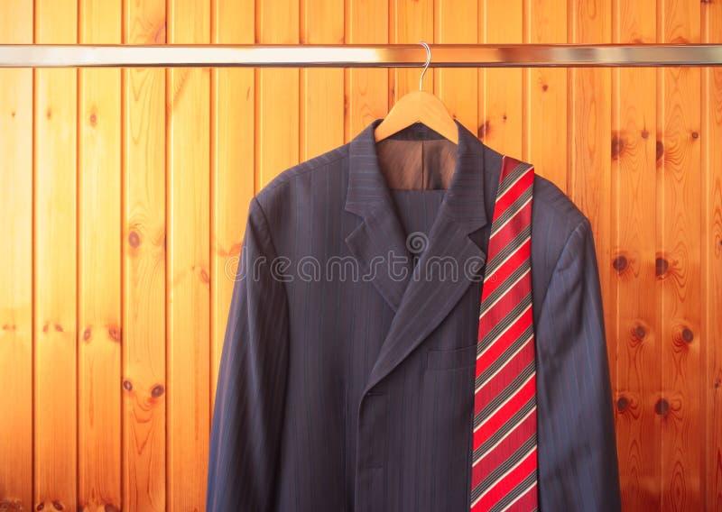 Κόκκινος ριγωτός δεσμός ατόμων κοστούμι και στην κρεμάστρα στο ξύλινο υπόβαθρο στοκ φωτογραφία
