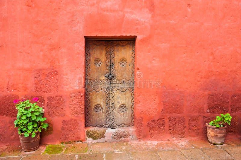 Κόκκινος τοίχος και παλαιά ξύλινη πόρτα στοκ φωτογραφία με δικαίωμα ελεύθερης χρήσης