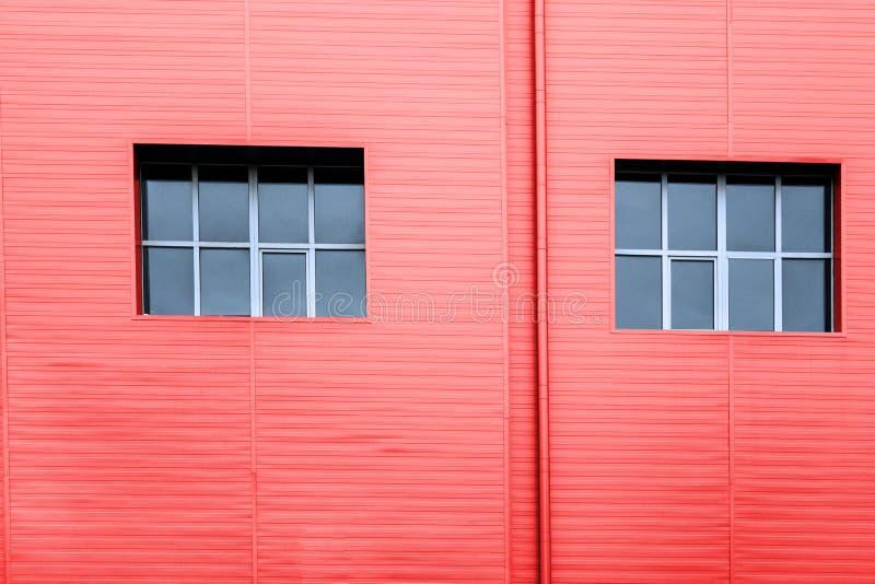 Κόκκινος τοίχος προσόψεων με δύο παράθυρα με την αντανάκλαση του ουρανού Διαστημικό σχέδιο γραμμών δομών αντιγράφων Η βιομηχανική στοκ φωτογραφίες