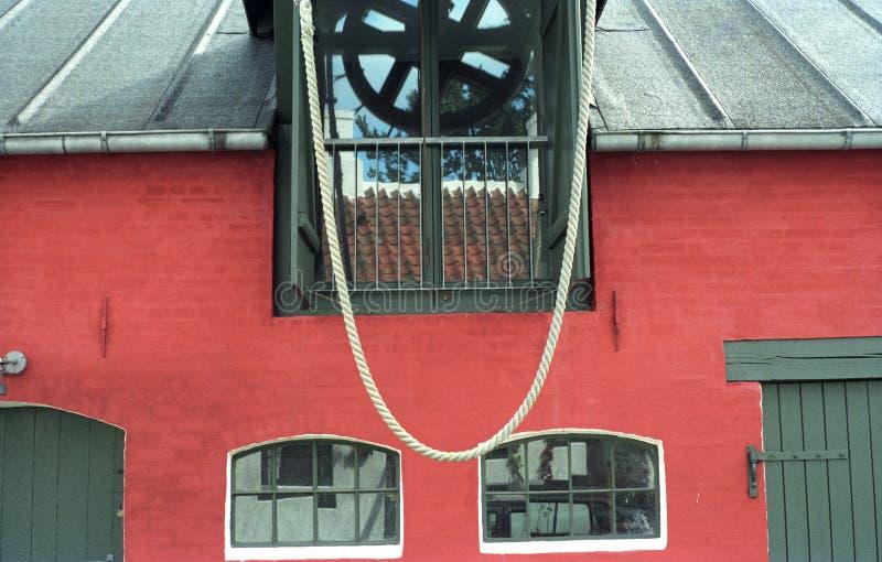 Κόκκινος τοίχος τούβλου και πράσινα παράθυρα στοκ φωτογραφίες