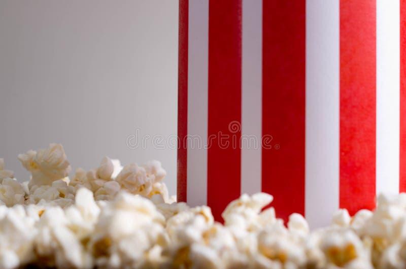 Κόκκινο άσπρο ριγωτό κιβώτιο εμπορευματοκιβωτίων κινηματογραφήσεων σε πρώτο πλάνο που στέκεται επάνω με popcorn που βρίσκεται γύρ στοκ εικόνα
