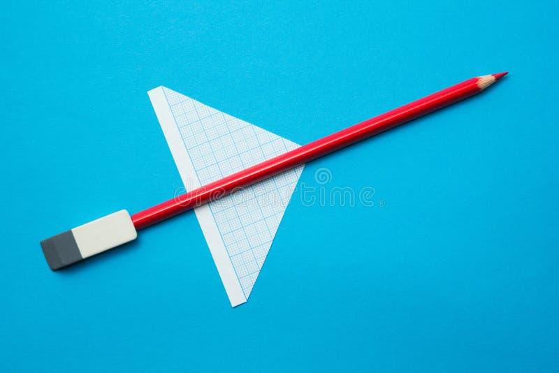 Κόκκινο αεροπλάνο φιαγμένο από μολύβια και έγγραφο για ένα μπλε υπόβαθρο o r στοκ εικόνα