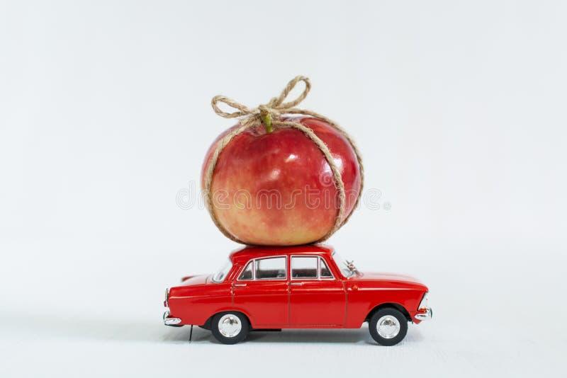 Κόκκινο αυτοκίνητο παιχνιδιών με το κόκκινο μήλο στη στέγη στοκ εικόνα