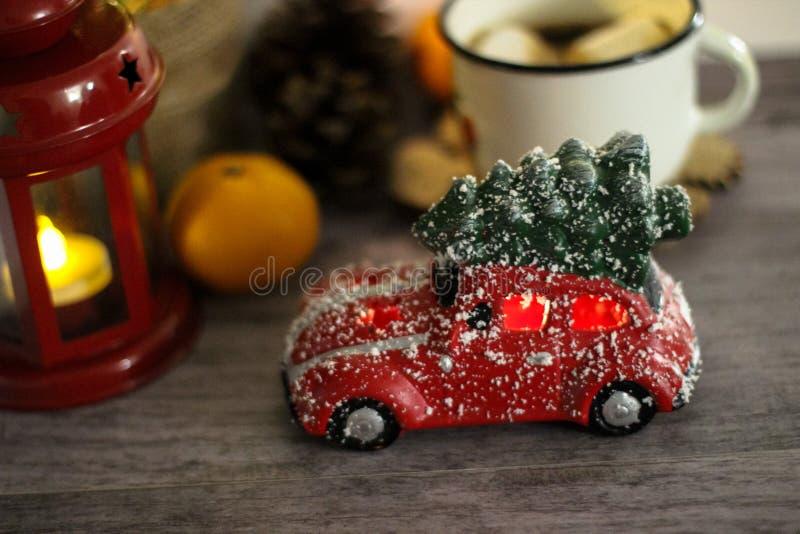 Κόκκινο αυτοκίνητο παιχνιδιών με το χριστουγεννιάτικο δέντρο στη στέγη Έννοια διακοπών στοκ εικόνες με δικαίωμα ελεύθερης χρήσης