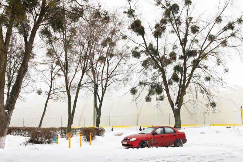 Κόκκινο αυτοκίνητο στο χιόνι κοντά στην εσωτερική παιδική χαρά στοκ φωτογραφίες με δικαίωμα ελεύθερης χρήσης