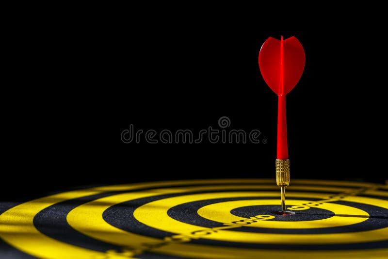Κόκκινο βέλος βελών στο κέντρο του dartboard Απομονωμένος στη μαύρη ΤΣΕ στοκ εικόνα
