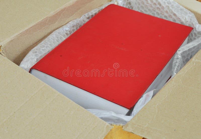 Κόκκινο βιβλίο στο κιβώτιο καφετιού εγγράφου στοκ φωτογραφία με δικαίωμα ελεύθερης χρήσης