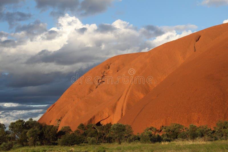 Κόκκινο βουνό σε αντίθεση με την πράσινους πεδιάδα και το μπλε ουρανό στοκ φωτογραφίες