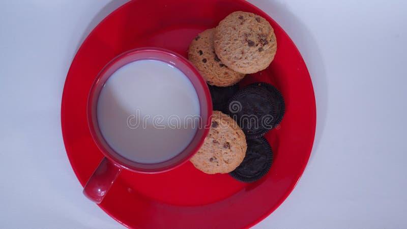 Κόκκινο γυαλί που γεμίζουν με το γάλα και το πιάτο και τα μπισκότα στοκ φωτογραφία