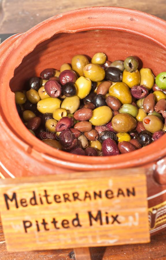 Κόκκινο δοχείο αργίλου που γεμίζουν με τις μεσογειακές, μικτές, κοιλαμένες ελιές στοκ φωτογραφία