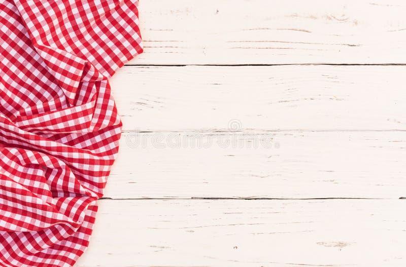 Κόκκινο ελεγχμένο τραπεζομάντιλο πικ-νίκ στην αριστερή πλευρά του άσπρου ξύλινου επιτραπέζιου υποβάθρου στοκ φωτογραφία με δικαίωμα ελεύθερης χρήσης