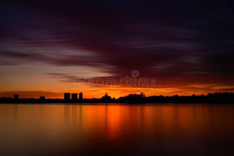 Κόκκινο ηλιοβασίλεμα του Βουκουρεστι'ου πέρα από τη λίμνη Herastrau, Ρουμανία στοκ φωτογραφίες