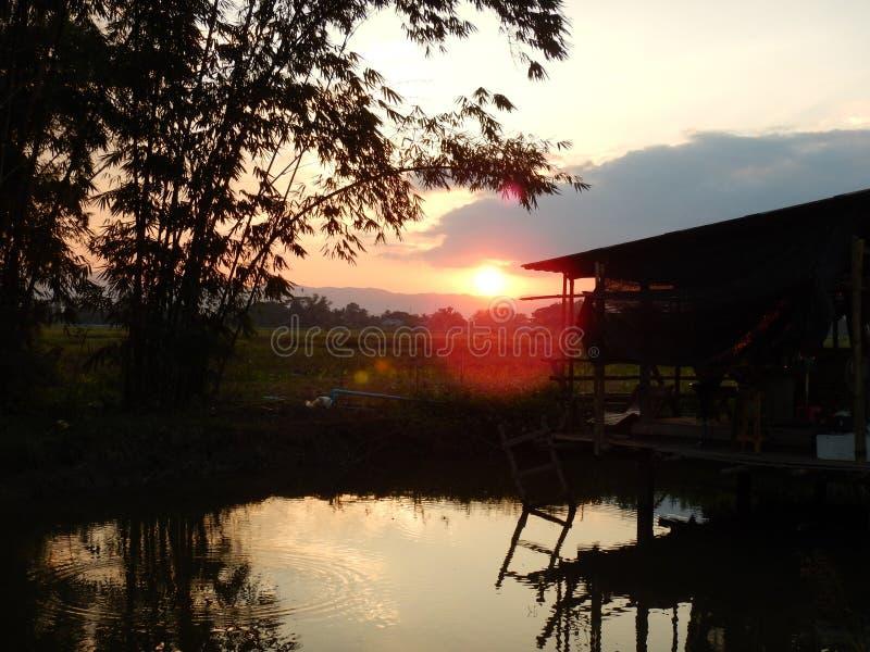 Κόκκινο ηλιοβασίλεμα που απεικονίζει από ένα ξύλινο επιπλέον σπίτι λιμνών στοκ εικόνες