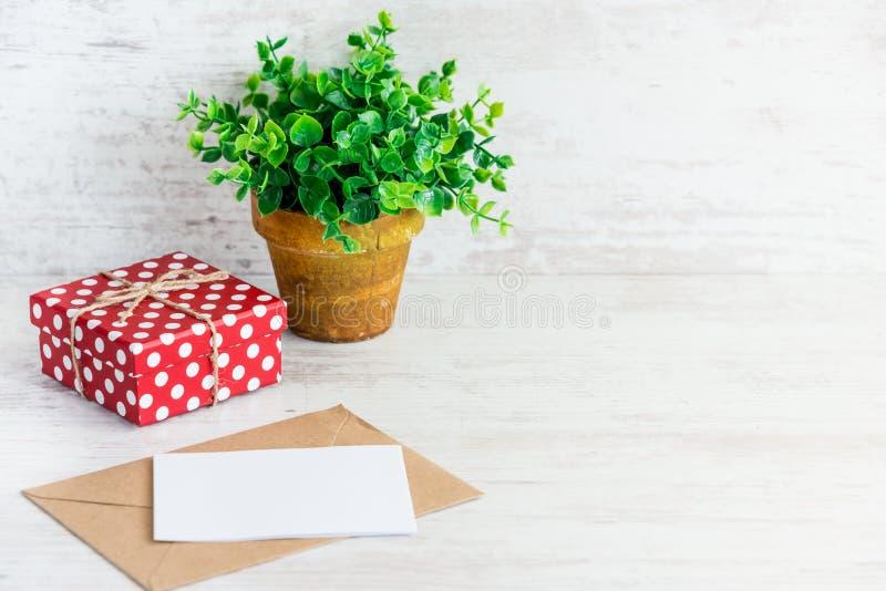 Κόκκινο διαστιγμένο κιβώτιο δώρων, κενή κάρτα, φάκελος του Κραφτ και ένα πράσινο λουλούδι σε ένα αγροτικό κεραμικό δοχείο Άσπρο ξ στοκ εικόνα με δικαίωμα ελεύθερης χρήσης
