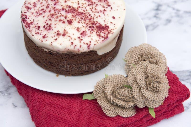 Κόκκινο κέικ βελούδου, με ένα κόκκινο ύφασμα στοκ φωτογραφίες