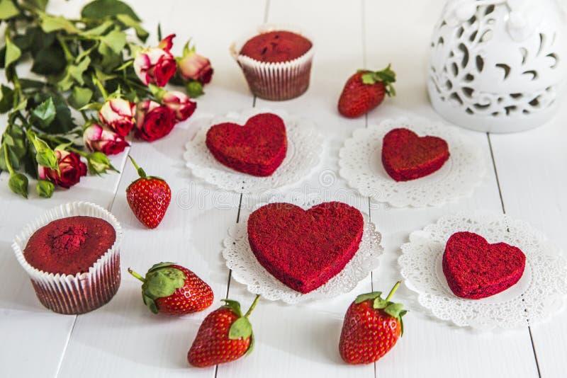 Κόκκινο κέικ χωρίς κόκκινο βελούδο ` κρέμας ` σε έναν άσπρο ξύλινο πίνακα, που διακοσμείται με τις φράουλες, τα τριαντάφυλλα και  στοκ φωτογραφία